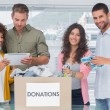 Smiling volunteers using tablet and taking out clothes from donations — Stock Photo