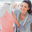 Stock Photo: Smiling fashion designer fixing dress on mannequin