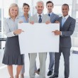 Business team holding large blank poster and smiling at camera — Stock Photo