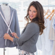Stock Photo: Attractive fashion designer measuring blazer lapel