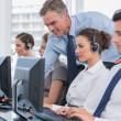 Smiling manager helping call centre agent — Stock Photo