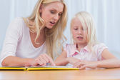 Mother and daughter reading a book together — Stock Photo