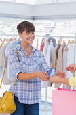 Cashier giving shopping bag and credit card — Stock Photo
