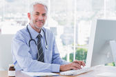 Doctor typing and using his computer — Stock Photo