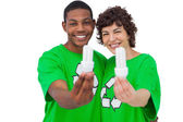 Two environmental activists holding energy saving light bulbs — Stock Photo