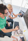 Cheerful photo editors working together on graphics tablet — Stock Photo