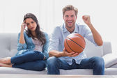 Woman annoyed by her partner watching basketball game — Stock Photo