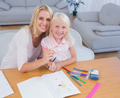 Mother and daughter drawing together and looking at camera — Stock Photo