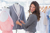 Attractive fashion designer measuring blazer — Stock Photo