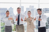Smiling team of business giving thumbs up — Stock Photo