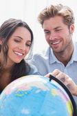 Happy couple looking at a globe — Stock Photo