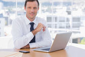 Smiling businessman leaning on his desk — Stock Photo