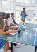 Creative designers listening a man doing a presentation — Stock Photo
