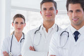 Three smiling doctors with lab coats — Stock Photo