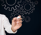 Businessman drawing white cogs and wheels — Stock Photo