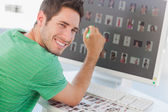 Cheerful photo editor pointing at his screen — Stock Photo