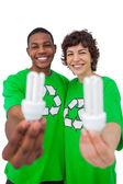 Activists holding energy saving light bulbs — Stock Photo