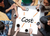 Team brainstorming over a poster with cost written on it — Stock Photo