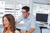 Smiling designers playing on a swivel chair — Stock Photo