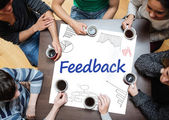 Feedback written on a poster with drawings of charts — Stock Photo