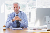 Serious doctor sitting at his desk — Stock Photo