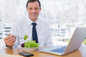 Happy businessman eating a salad on his desk — Stock Photo