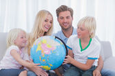 Family looking at globe together — Stock Photo