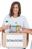 Smiling volunteer holding a food donation box — Stock Photo