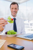 Businessman eating a salad — Stock Photo