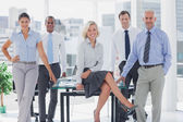 Attractive manger posing with colleagues around — Stock Photo