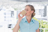 Businesswoman drinking from disposable coffee cup — Stock Photo