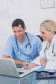 Two doctors working together on a laptop — Stock Photo