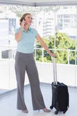 Smiling businesswoman on the phone leaning on suitcase — Stock Photo