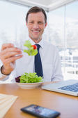 Cheerful businessman eating a salad — Stock Photo