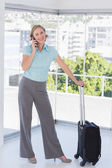 Smiling businesswoman on the phone with suitcase — Stock Photo