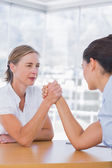 Rival businesswomen having an arm wrestle — Stock Photo