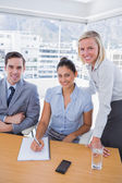 Business at desk with notepad smiling at camera — Stock Photo