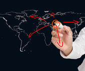 Businessman drawing world map with arrows — Stock Photo