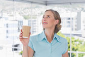 Businesswoman holding disposable coffee cup and looking up — Stock Photo