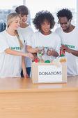 Dobrovolníci uvedení potravin v darované — Stock fotografie