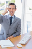 Smiling businessman on the phone looking at camera — Stock Photo