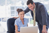 Smiling business working together with the same laptop — Stock Photo
