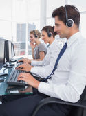 Group of call center employees working in line — Stock Photo