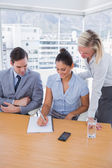 Happy businesswoman showing colleagues something on her notepad — Stock Photo