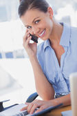 Happy businesswoman calling and smiling — Stock Photo