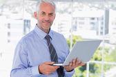 Uśmiechający się biznesmen posiadania laptopa — Zdjęcie stockowe