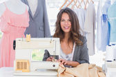 Smiling fashion designer using sewing machine — Stock Photo