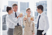 Smiling team of business clinking their flutes of champagne — Stock Photo