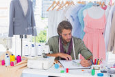 Handsome fashion designer drawing with pencils — Stock Photo