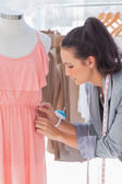 Pretty fashion designer fixing dress — Stock Photo
